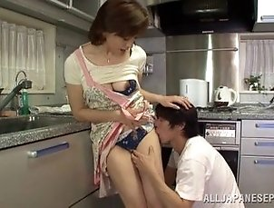 A mature Japanese babe cooks and fucks in the kitchen